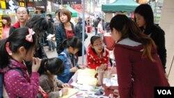 有家長帶同年幼子女參觀中國維權律師關注組的攤位,了解中國維權律師子女被當局剝奪人權的狀況 (美國之音湯惠芸)