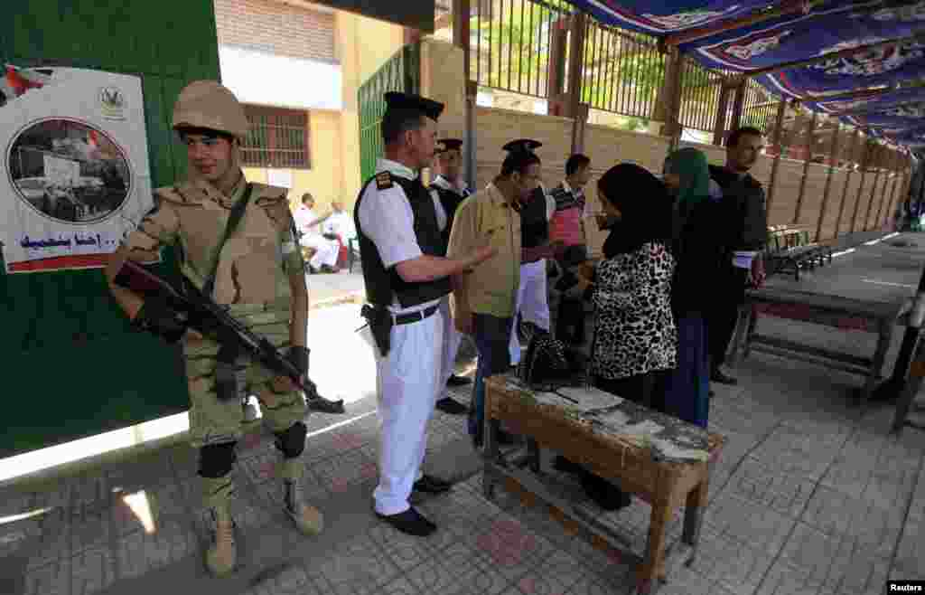 Voters present papers at a polling station in the El Sayda Zeinab area on the third day of voting in the Egyptian presidential elections in Cairo, May 28, 2014.