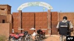Un gendarme nigérien se tient près des motocyclettes calcinées utilisées par les assaillants, devant la prison de Koutoukale, près de Niamey, suite à une attaque le 17 octobre 2016.
