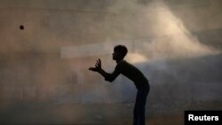 A boy is silhouetted against smoke while playing cricket in a littered ground in a slum area on the outskirts of Karachi, Pakistan, Oct. 18, 2011.