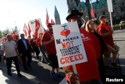 Members of Canada's Unifor union march past Parliament Hill during a rally ahead of the third round of NAFTA talks involving the United States, Mexico and Canada in Ottawa, Ontario, Sept. 22, 2017.