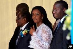 Zimbabwean First Lady Grace Mugabe, center, walks with Zimbabwean President Robert Mugabe at a ceremony to rename Harare International airport to Robert Gabriel Mugabe International Airport in Harare, Thursday, Nov. 9, 2017.