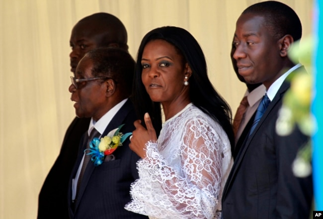 Zimbabwean First Lady Grace Mugabe, center, walks with Zimbabwean President Robert Mugabe at a ceremony to rename Harare International airport to Robert Gabriel Mugabe International Airport in Harare, Thursday, Nov. 9, 2017.