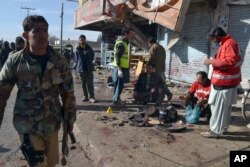 Pakistani police officers and rescue workers gather at the site of suicide bombing in Quetta, Pakistan, Jan. 13, 2016.