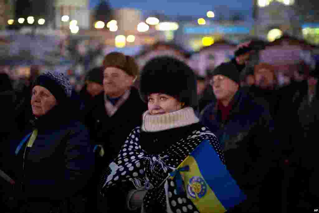 People, one with a Ukrainian flag, attend a political speech on a stage set in Kyiv's Independence Square, the epicenter of the country's current unrest.