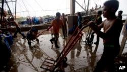 Buruh migran membongkar hasil tangkapannya di wilayah barat Bangkok. (20/6). Turunnya status Thailand dalam perdagangan manusia bisa berdampak negatif terhadap industri perikanan dan udang negara itu di mana AS adalah pasar utamanya.