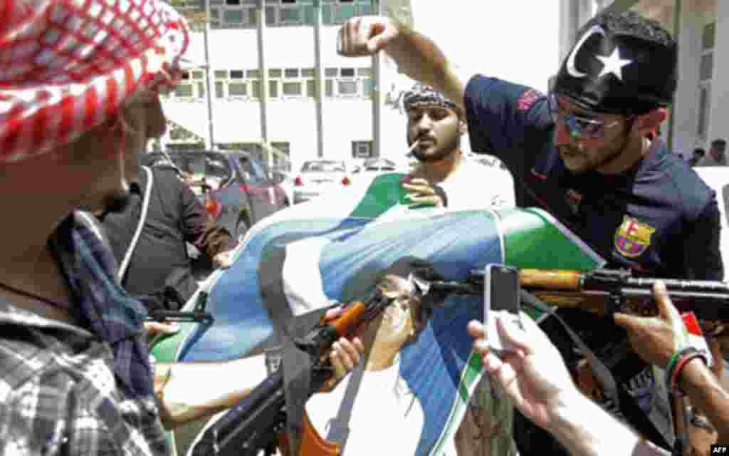Повстанцы снимают портрет Каддафи, правившего страной 42 года. 22 августа 2011г. Reuters
