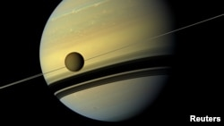 Titan, Saturn's largest moon appears before the planet as it undergoes seasonal changes in this natural color view from NASA's Cassini spacecraft in this handout released by NASA August 29, 2012. The moon measures 3,200 miles, or 5,150 kilometers, across