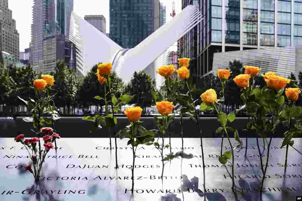 ផ្កាត្រូវបានគេដាក់នៅក្បែរឈ្មោះអ្នកដែលបានស្លាប់ ដែលដាក់បង្ហាញនៅឯសារមន្ទីរជាតិនិងទីរំឭកវិញ្ញាណក្ខន្ធជនដែលបានស្លាប់កាលពីថ្ងៃទី១១ ខែកញ្ញា ឆ្នាំ២០០១ (National September 11 Memorial and Museum) នៅថ្ងៃសុក្រ ទី១១ ខែកញ្ញា ឆ្នាំ២០២០ នៅទីក្រុងញូវយ៉ក។ (AP)