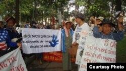 Tại một cuộc biểu tình, người dân cầm biểu ngữ tố cáo các quan chức nhà nước tham nhũng, cướp đất dân nghèo.