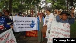 Người biểu tình cầm biểu ngữ tố cáo các quan chức nhà nước tham nhũng, cướp đất của dân nghèo.