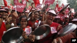 Demonstrators shout slogans as they hold steel plates during a protest against food prices in New Delhi, Feb. 23, 2011.