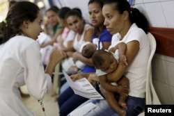 FILE - Mothers with their children, who have microcephaly, await medical care at the Hospital Oswaldo Cruz, in Recife, Brazil, Jan. 26, 2016.