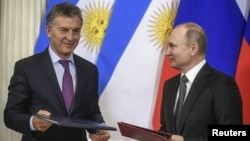 FILE - Russian President Vladimir Putin, right, and his Argentinian counterpart Mauricio Macri attend a signing ceremony following their talks at the Kremlin in Moscow, Russia, Jan. 23, 2018.