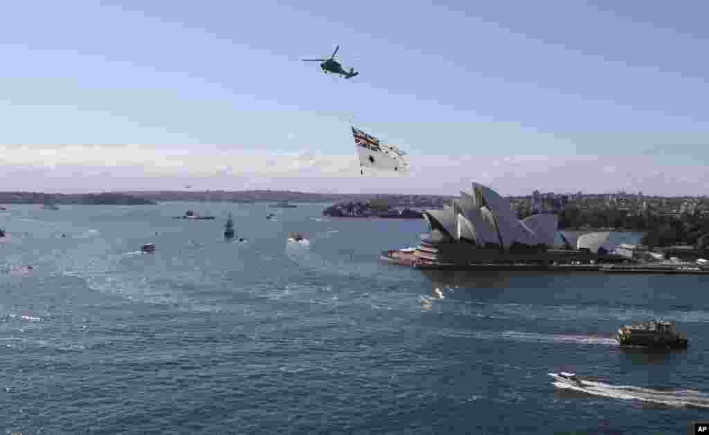 A Royal Australian Navy helicopter towing the Australian naval ensign passes over the Opera House during the International Fleet review, Sydney, Oct. 4, 2013.