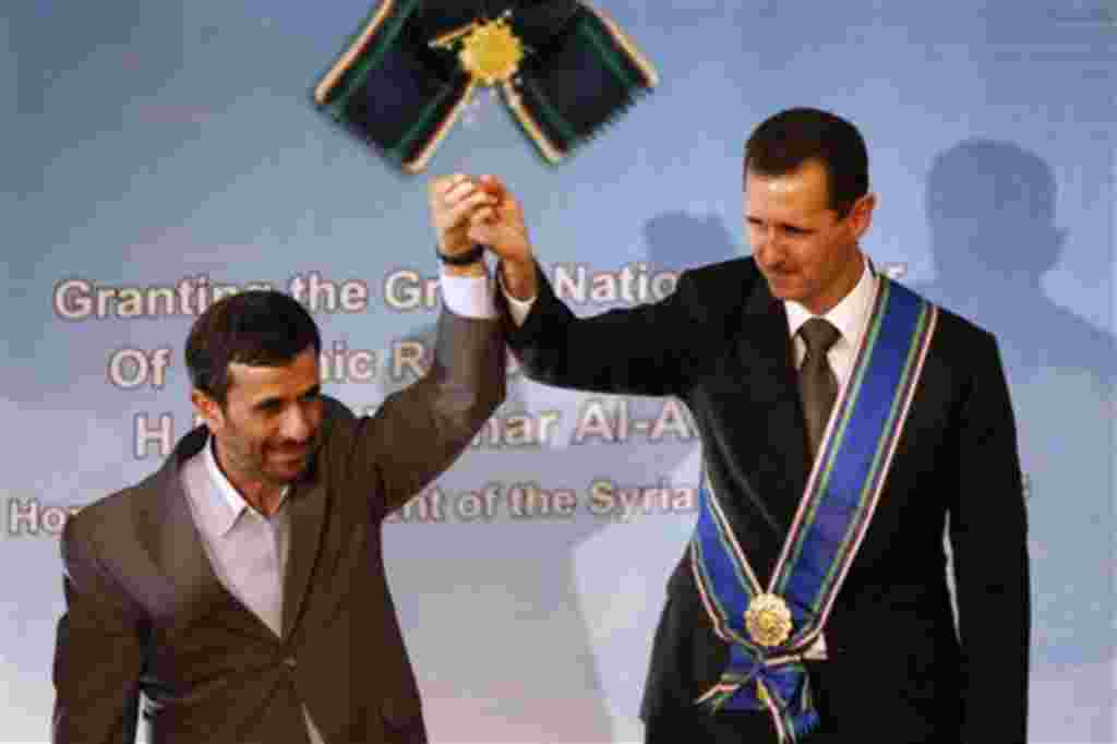 FILE - In this Oct. 2, 2010 file photo, Iranian President Mahmoud Ahmadinejad, left, holds up the hand of his Syrian counterpart Bashar Assad after he awarded Iran's highest national medal to Assad, in a ceremony in Tehran, Iran. When Syria's president la