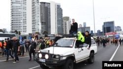 Construction workers and far right activists protest against coronavirus disease (COVID-19) restrictions on the West Gate Freeway in Melbourne, Australia, Sept. 21, 2021.