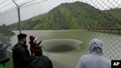 People stop to watch water flow into the iconic Glory Hole spillway at the Monticello Dam, Feb. 20, 2017, in Lake Berryessa, Calif. Water is flowing for the first time in over a decade into the 72-foot diameter hole due to the recent storms in California.