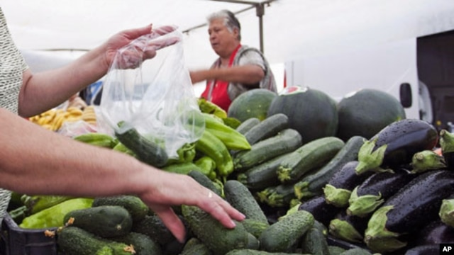 A woman buys cucumbers at a market in El Alquian, Almeria, in southeastern Spain, May 29, 2011