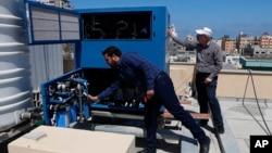 Ichimlik suvi ishlab chiqaruvchi generator kasalxona tomiga o'rnatilmoqda, G'azo, Falastin, 2020-yil, 30-aprel