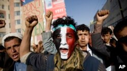 FILE - A Houthi Shi'ite rebel with Yemen's flag painted on his face chants slogans during a rally in the capital, Sana'a, Yemen.