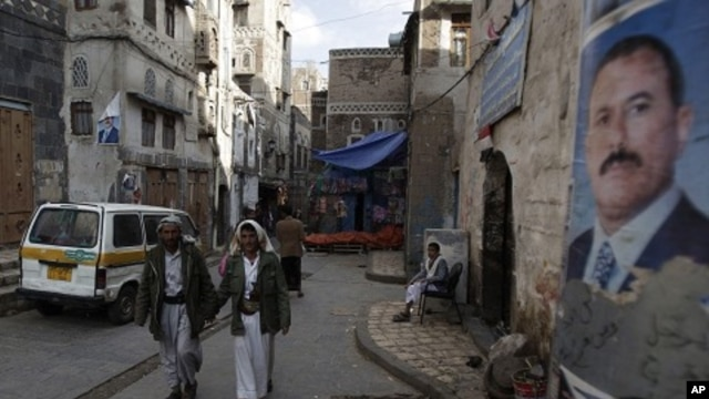 People walk along a street where posters hang of Yemen's President Ali Abdullah Saleh in the old city of Sanaa, Yemen, August 7, 2011