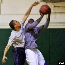 Presiden Barack Obama berusaha memblok tembakan saat bermain basket (foto dokumentasi).