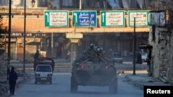 FILE - Russian soldiers in armored vehicles patrol a street in Aleppo, Syria, Feb. 2, 2017.