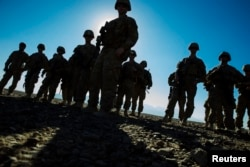 FILE - U.S. soldiers from Dragon Company of the 3rd Cavalry Regiment are silhouetted as they stand outside their vehicles during a mortar exercise near forward operating base Gamberi in the Laghman province of Afghanistan, Dec. 26, 2014.