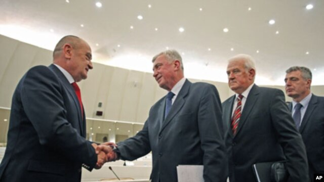 Bosnia's new Prime Minister Vjekoslav Bevanda (L) receives congratulations from members of parliament, in Sarajevo, January 12, 2012.