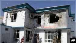 星期一﹐一名美軍士兵和阿富汗的安全人員檢查在坎大哈遭到襲擊的聯合國建築物