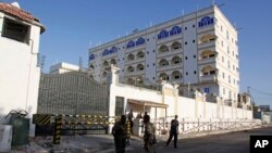 FILE - Somali soldiers stand outside the Jazeera Hotel in Mogadishu, Somalia, Thursday, Jan. 2, 2014.
