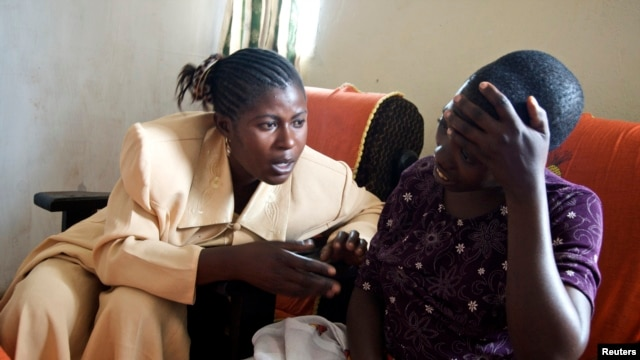 FILE - Apollonie, a Congolese counselor, speaks with a rape victim in the HEAL Africa hospital in Goma.