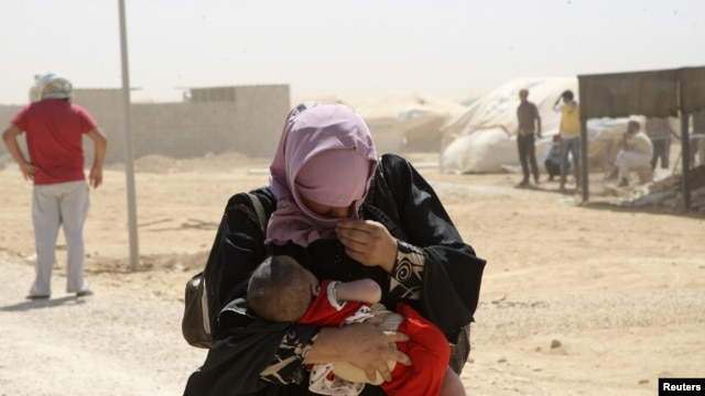 A Syrian refugee woman carries her baby as they walk amidst dust at the Al Zaatri refugee camp in the Jordanian city of Mafraq, near the border with Syria, August 13, 2012.