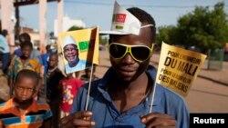 Muunga mkono wa mgombea Ibrahim Boubacar Keita akishikilia bendera kabla ya chama chake.
