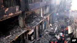 Penduduk setempat dan petugas pemadam kebakaran berkumpul di sekitar bangunan yang hangus akibat kebakaran di Dhaka, Bangladesh, 21 Februari 2019.