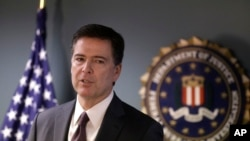 FILE - FBI Director James Comey takes questions from members of the media during a news conference in Boston.