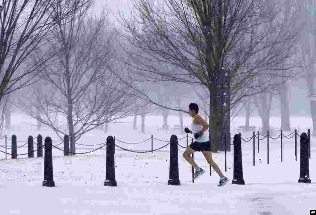 An unidentified man braves the elements to run on the National Mall as snow falls in Washington, prompting area schools and the U.S. federal government to close.