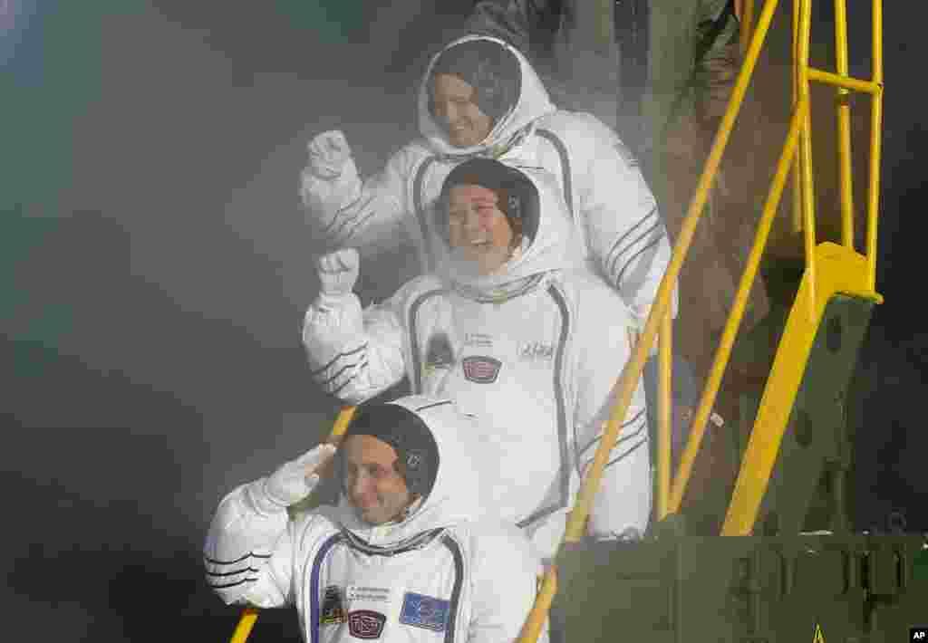 លោក Anton Shkaplerov អាកាសយានិករុស្ស៊ី លោក Scott Tingle អាកាសយានិកអាមេរិកាំង និងលោក Norishige Kanai អាកាសយានិកជប៉ុន បក់ដៃនៅក្បែរកន្លែងបាញ់រ៉ុក្កែត Soyuz-FG។