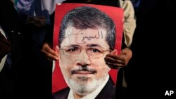 "A supporter holds a poster of Egypt's Islamist President Mohammed Morsi with Arabic that reads, ""Sisi traitor,"" during a rally, in Nasser City, Cairo, Egypt, July 4, 2013."