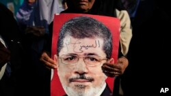 "A supporter holds a poster of Egypt's Islamist President Mohamed Morsi with Arabic that reads, ""Sisi traitor,"" during a rally, in Nasser City, Cairo, July 4, 2013."