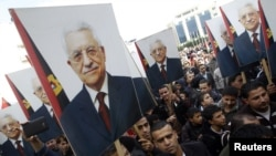 Palestinians hold placards of President Mahmoud Abbas during a rally in support of his efforts to secure a diplomatic upgrade at the United Nations, Ramallah, West Bank, November 25, 2012.