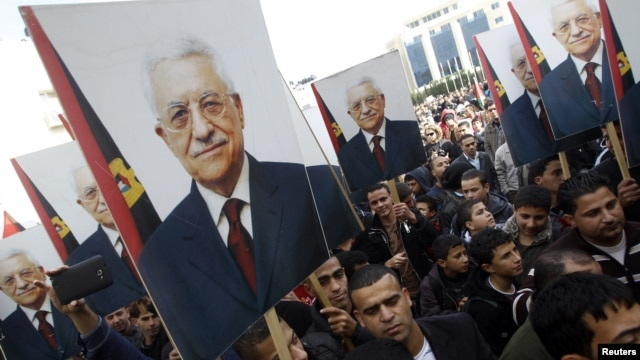 Palestinians hold placards depicting President Mahmoud Abbas during a rally in support of his efforts to secure a diplomatic upgrade at the United Nations, in the West Bank city of Ramallah, November 25, 2012.