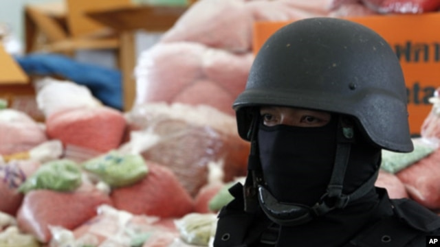 A policeman stands guard near bags of methamphetamine pills during the 39th Destruction of Confiscated Narcotics in Ayutthaya province, nearly 80 km (50 miles) north of Bangkok, June 24, 2011. About 5,844 kg (12,884 lbs) of drugs, among them methamphetami