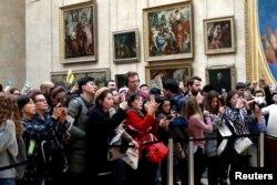 بازدیدکنندگان لوور در مقابل تابلوی موتا لیزا