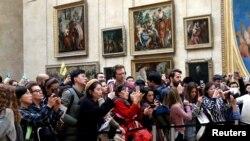 Visitantes del Museo del Louvre, en París, toman fotos de la Mona Lisa de Leonardo Da Vinci, el 3 de diciembre de 2018.