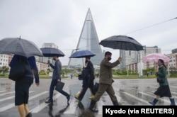 Orang-orang yang memakai masker pelindung berjalan di tengah kekhawatiran atas COVID-19 di Pyongyang, Korea Utara, 15 Mei 2020, dalam foto yang dirilis oleh Kyodo. (Foto: Kyodo via REUTERS)