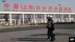FILE - Security guards patrol the main gate of the China (Shanghai) Pilot Free Trade Zone at the Pudong International Airport in Shanghai, China.