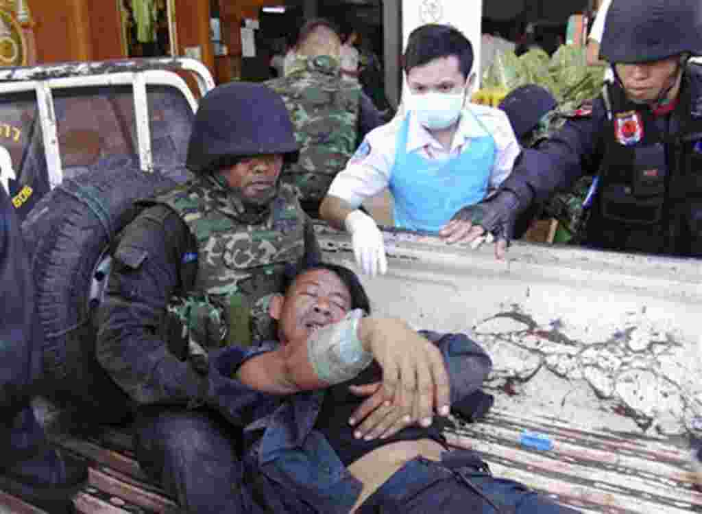 A Thai soldier injured in a fighting with Cambodia is helped by his comrades and a nurse after arriving at a hospital in Phnom Dongrak district of Surin province, northeastern Thailand, April 22, 2011