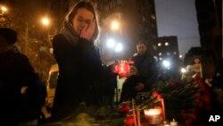 Une femme dépose une bougie à Moscou en Russie, le 25 décembre 2016.